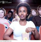 african_woman_eating_popcorn_in_movie_theater_BLD082235