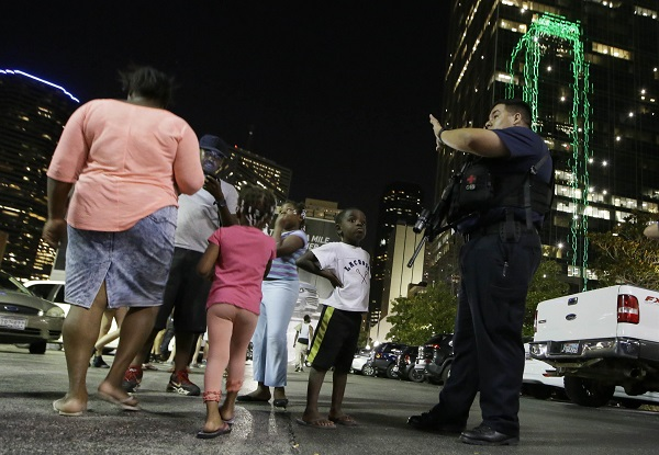 Dallas police order people away from the area after several police were shot in downtown Dallas, Thursday, July 7, 2016. (AP Photo/LM Otero)