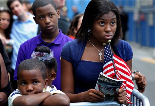 Teneal Colbert, 15, right, her brother Fredrick Meeks, 9, left and brother Tyrus Colbert, 14,  top left, of Garden City, N.Y., watch a large monitor broadcasting ceremonies near the World Trade Center site Sunday, Sept. 11, 2011 as the 10th anniversary of the attacks on the World Trade Center is marked in New York. (AP Photo/Craig Ruttle)