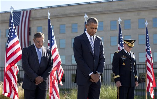 President Barack Obama, flanked by Defense Secretary Leon Panetta, left, and Joint Chiefs Chairman Gen. Martin Dempsey, bow their heads at the Pentagon Memorial,Tuesday, Sept. 11, 2012, during a ceremony to mark the 11th anniversary of the Sept. 11 attacks. (AP Photo/Carolyn Kaster)
